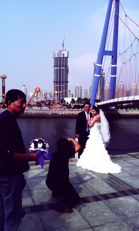 Chinese Wedding in Dalian: Bride and Groom are directed by photographers under Xinghai bridge